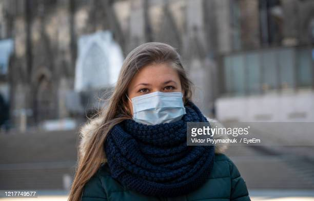 portrait of young woman wearing surgical mask standing by church outdoors - coronavirus winter stock pictures, royalty-free photos & images