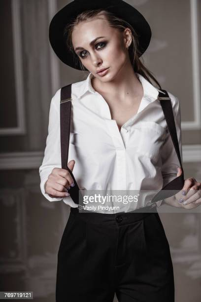 portrait of young woman wearing suspenders standing against wall - サスペンダー ストックフォトと画像