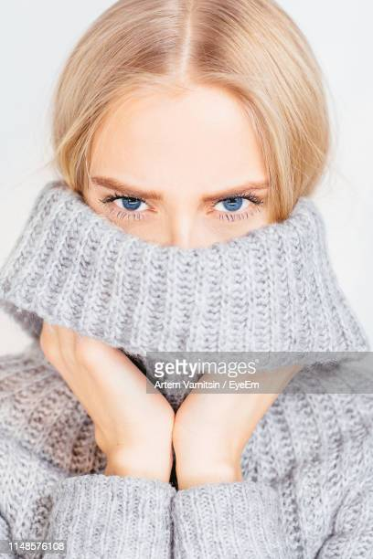 portrait of young woman wearing sweater against white background - turtleneck stock pictures, royalty-free photos & images
