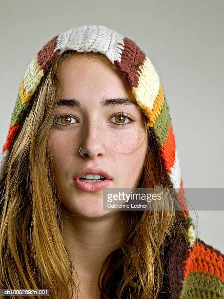 Portrait of young woman wearing sweater with hood, studio shot