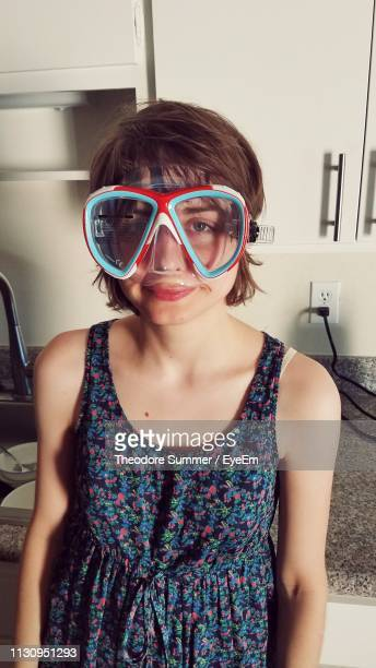 portrait of young woman wearing swimming goggles while standing at home - ノースリーブワンピース ストックフォトと画像