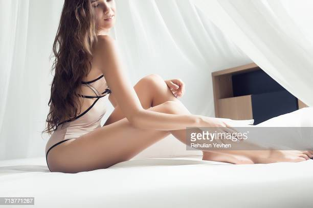 portrait of young woman wearing swimwear, sitting on bed in provocative pose - beautiful asian legs stock photos and pictures