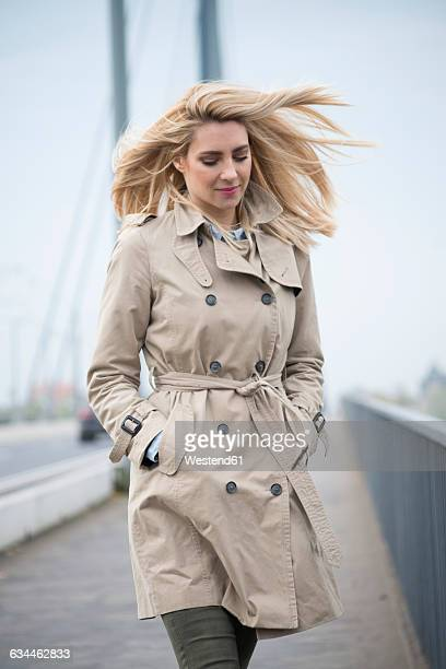 Portrait of young woman wearing trench coat walking on a bridge