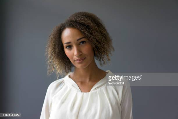 portrait of young woman wearing white blouse against grey background - 白い服 ストックフォトと画像