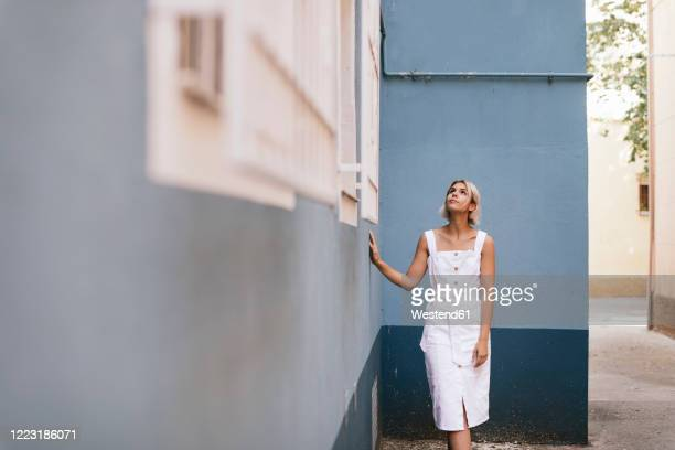 portrait of young woman wearing white summer dress looking up - サンドレス ストックフォトと画像