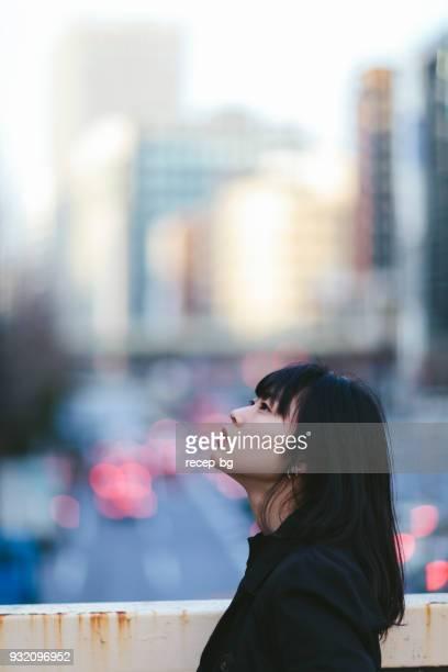 市内見ながら若い女性の肖像画 - 見上げる ストックフォトと画像