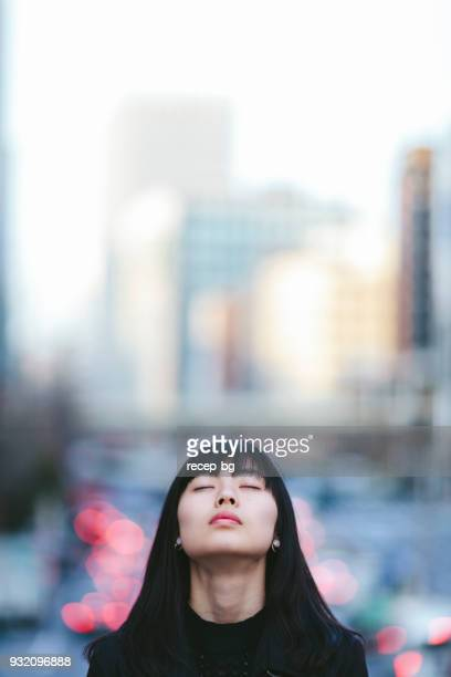 portrait of young woman whileher eyes are closed in the city - imagination stock pictures, royalty-free photos & images