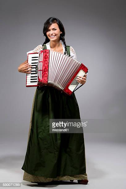 portrait of young woman with accordion wearing dirndl - accordion instrument stock pictures, royalty-free photos & images