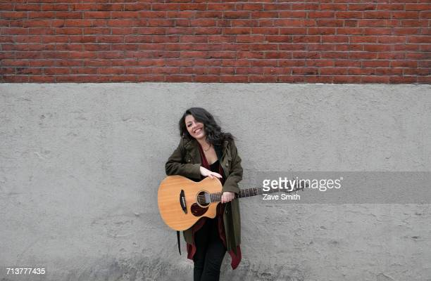 portrait of young woman with acoustic guitar leaning against wall - maxim musician stock photos and pictures