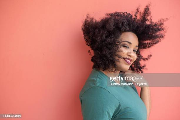 portrait of young woman with afro hairstyle - frizzy stock pictures, royalty-free photos & images