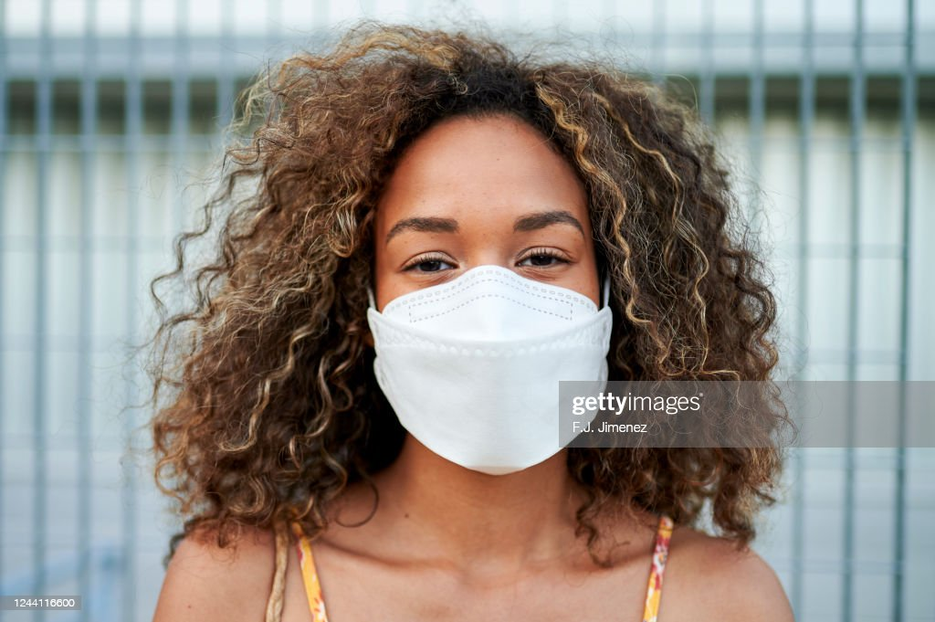 Portrait of young woman with antiviral mask outdoors : Stock Photo