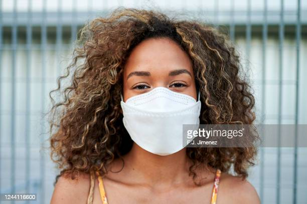 portrait of young woman with antiviral mask outdoors - cubrebocas fotografías e imágenes de stock
