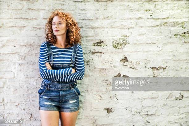portrait of young woman with arms crossed leaning against white brick wall - calção - fotografias e filmes do acervo