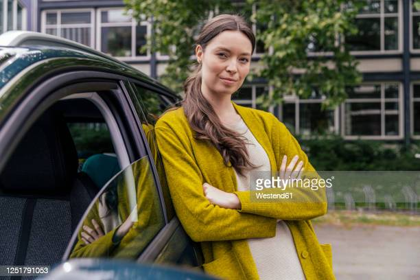 portrait of young woman with arms crossed leaning at her car - arme verschränkt stock-fotos und bilder