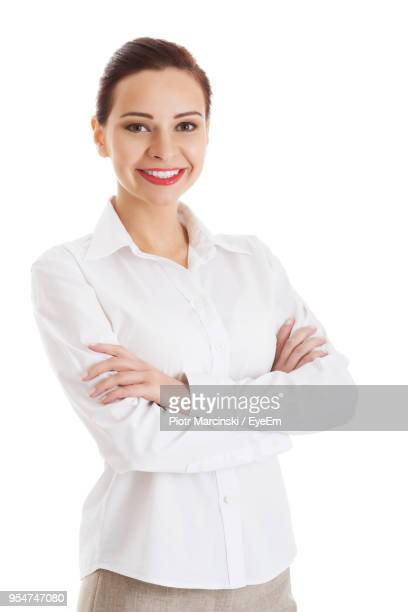 portrait of young woman with arms crossed standing against white background - all shirts ストックフォトと画像