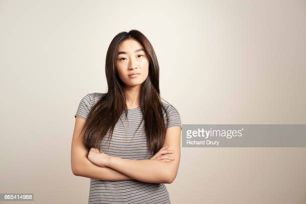 portrait of young woman with arms folded - attitude stock pictures, royalty-free photos & images