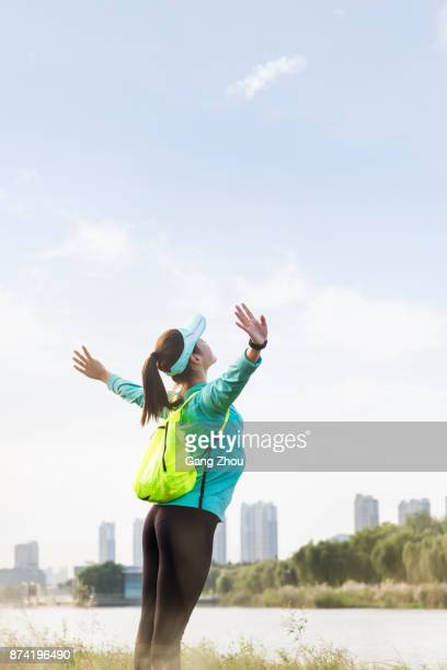 portrait of young woman with arms outstretched by lakeside