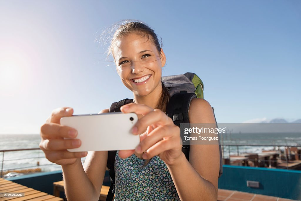 Portrait of young woman with backpack and smartphone : Foto stock