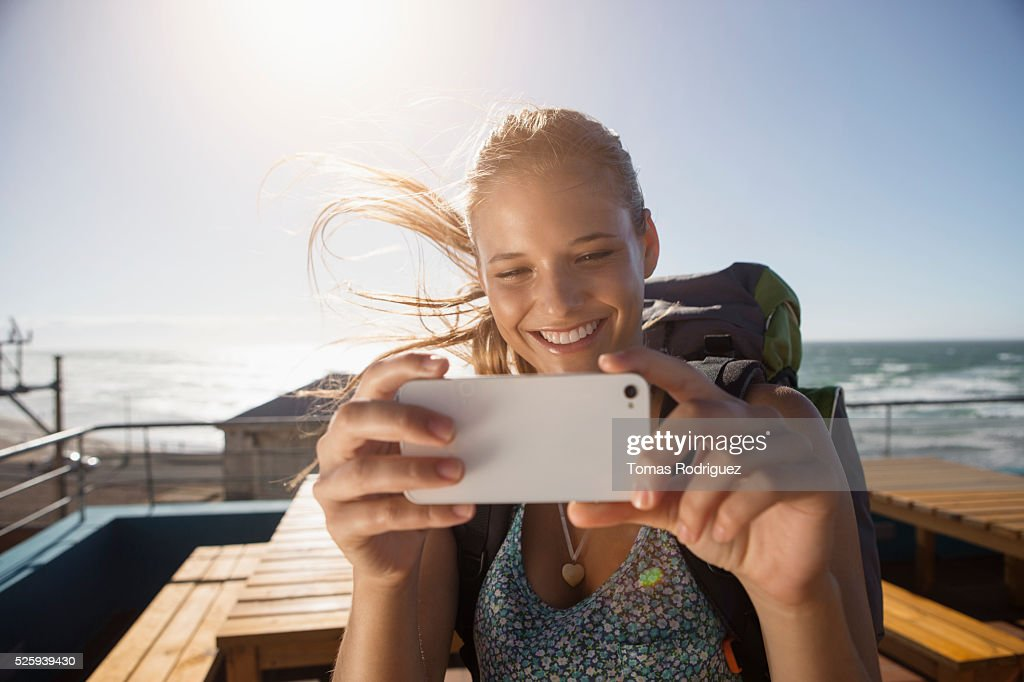 Portrait of young woman with backpack and smartphone : Stock Photo