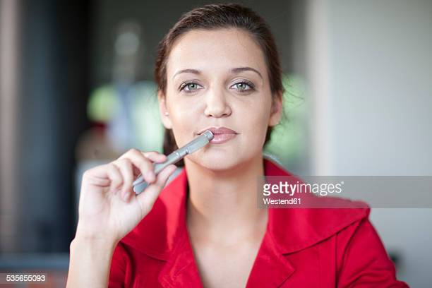 Portrait of young woman with ballpen