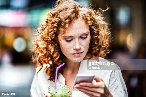 portrait of young woman with beverage looking at cell phone - junge frau allein fotos stock-fotos und bilder