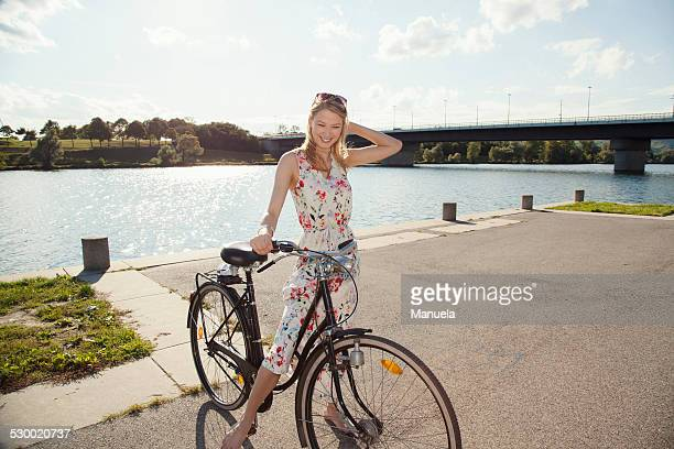 Portrait of young woman with bicycle on riverside, Danube Island, Vienna, Austria