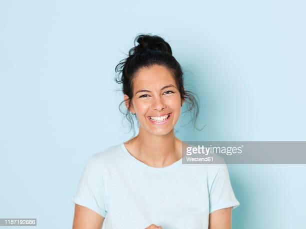 portrait of young woman with black hair, light blue background - schwarzes haar stock-fotos und bilder