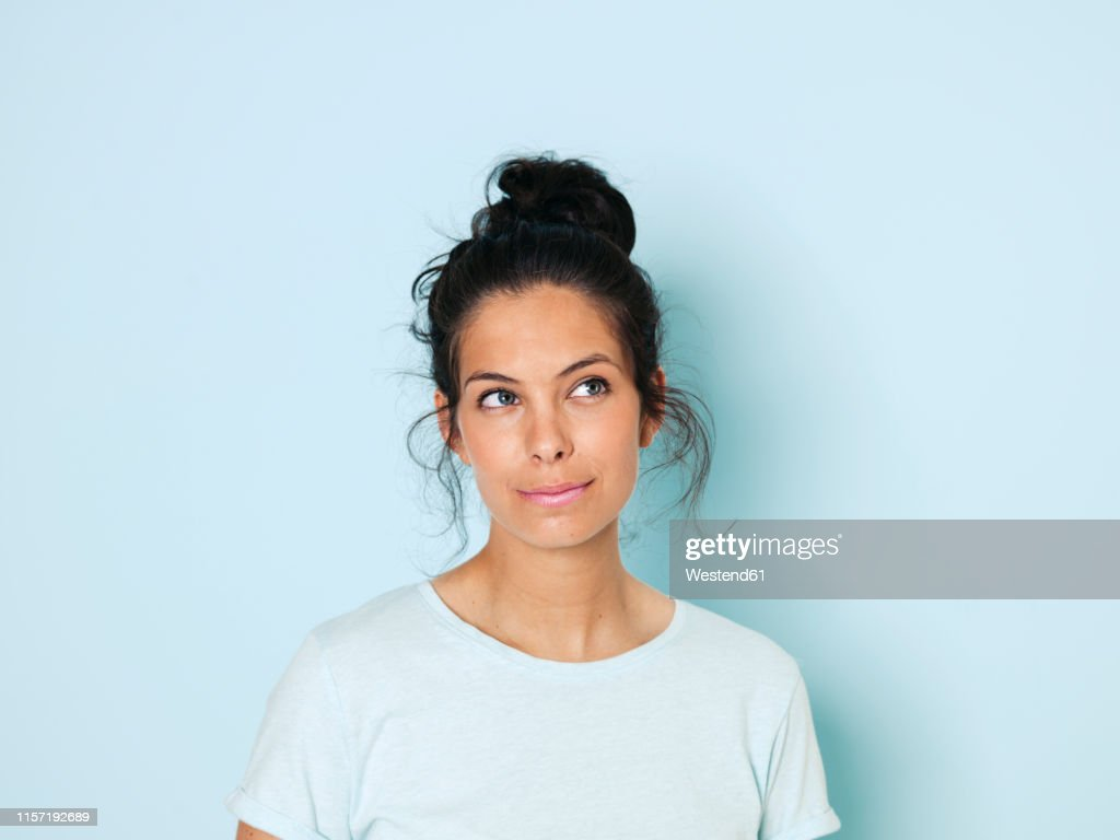 Portrait of young woman with black hair, light blue background : Stock Photo