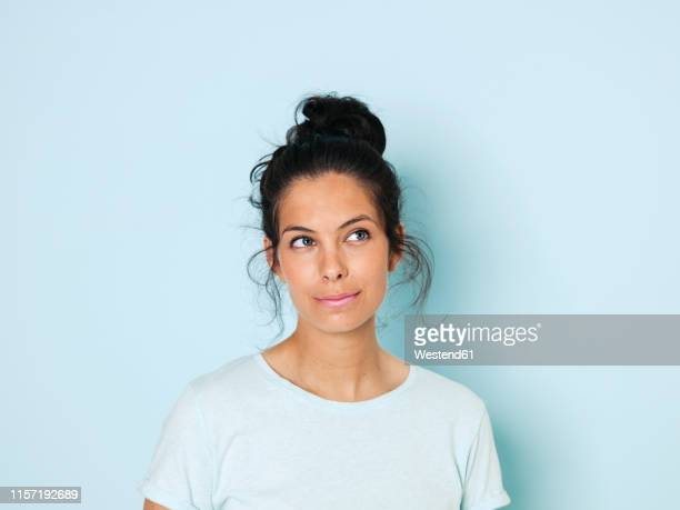 portrait of young woman with black hair, light blue background - sfondo a colori foto e immagini stock