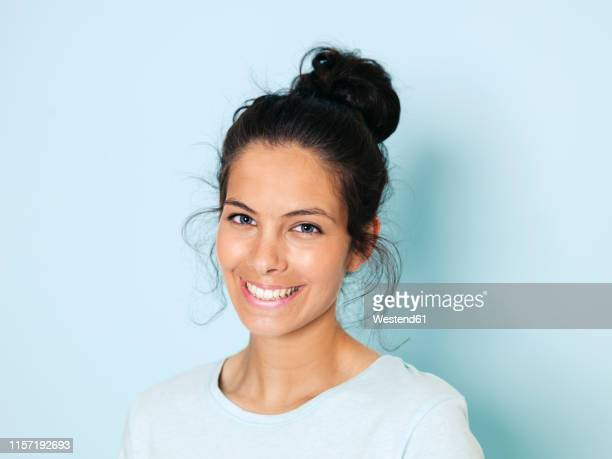 portrait of young woman with black hair, light blue background - おだんごヘア ストックフォトと画像