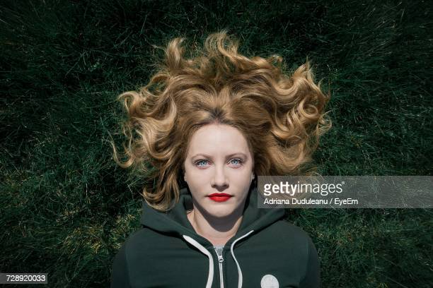 portrait of young woman with blond hair lying down on grassy field - lying down stock-fotos und bilder