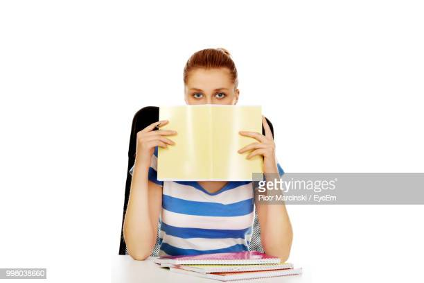 Portrait Of Young Woman With Book Sitting On Chair Against White Background
