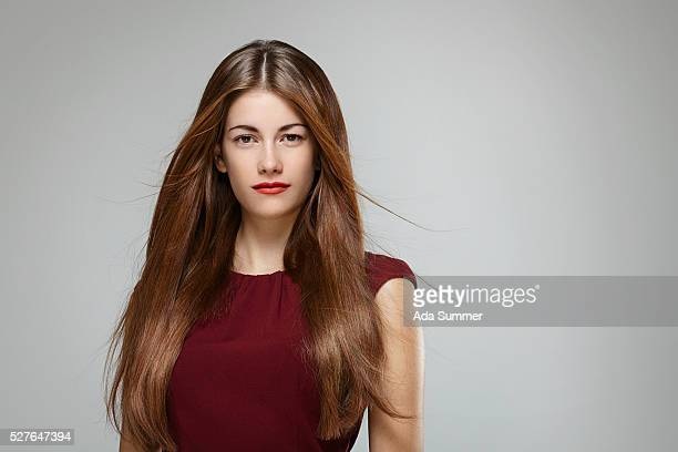 portrait of young woman with brown long hair wearing red dress - steil haar stockfoto's en -beelden