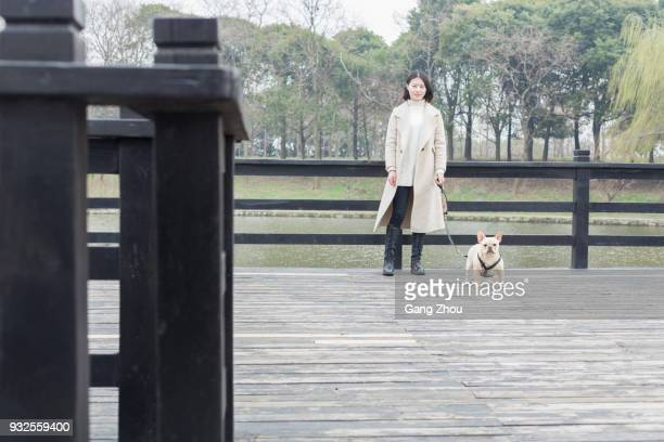 portrait of young woman with bulldog on footbridge - chinese bulldog stock pictures, royalty-free photos & images