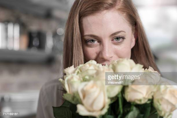 Portrait of young woman with bunch of roses