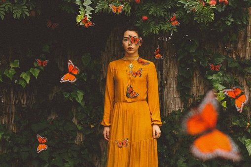 Portrait Of Young Woman With Butterflies Standing At Park - gettyimageskorea
