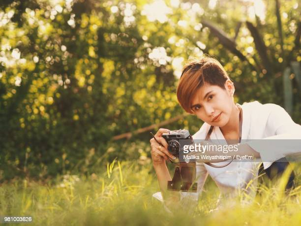 Portrait Of Young Woman With Camera On Field