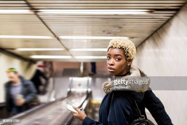 portrait of young woman with cell phone on escaltor in underground station - attitude stock pictures, royalty-free photos & images