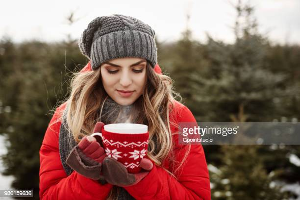 Portrait of young woman with coffee in christmas tree forest