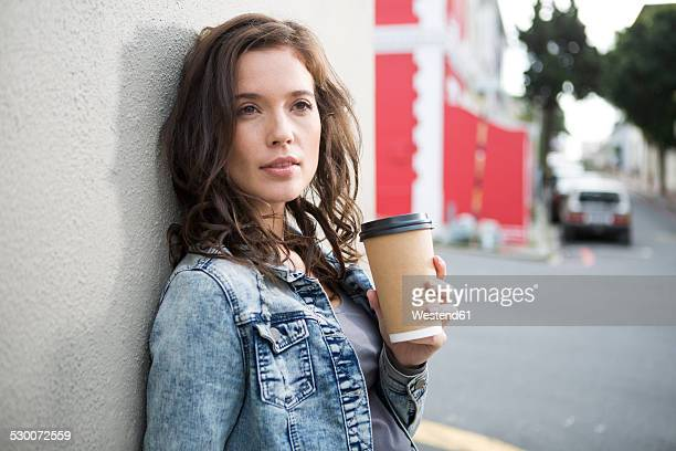 Portrait of young woman with coffee to go leaning at house front