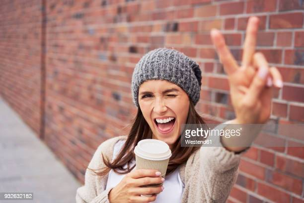 Portrait of young woman with coffee to go showing victory sign