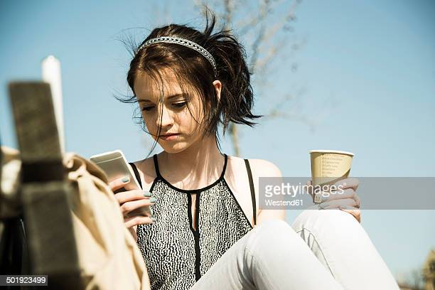 Portrait of young woman with coffee to go using smartphone