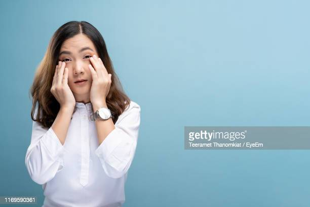 portrait of young woman with conjunctivitis against blue background - conjunctivitis stock pictures, royalty-free photos & images