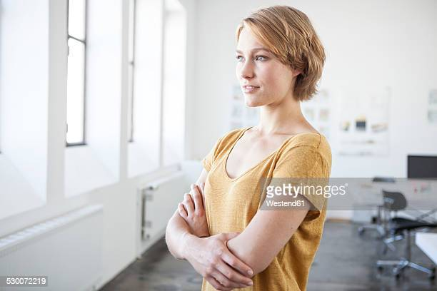 portrait of young woman with crossed arms in a creative office - wegkijken stockfoto's en -beelden