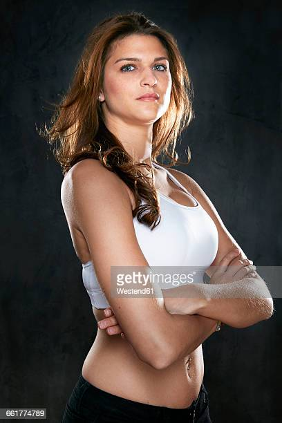 portrait of young woman with crossed arms in front of dark background - one young woman only stock pictures, royalty-free photos & images