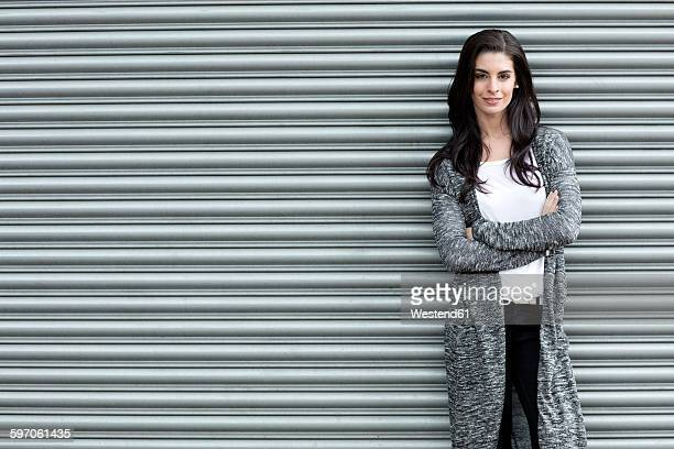 portrait of young woman with crossed arms standing in front of roller shutter - roller shutter stock pictures, royalty-free photos & images