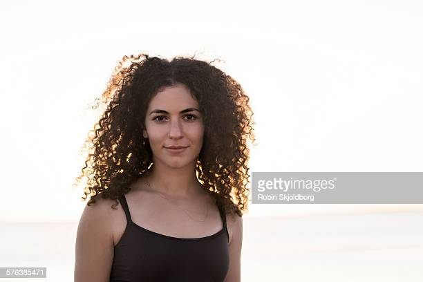 portrait of young woman with curly hair in sunset - spaghetti straps stock pictures, royalty-free photos & images