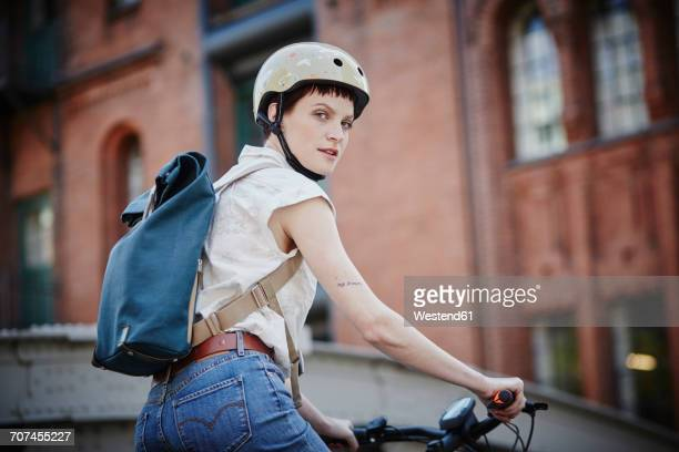 portrait of young woman with cycling helmet and backpack on electric bicycle - sportschutzhelm stock-fotos und bilder