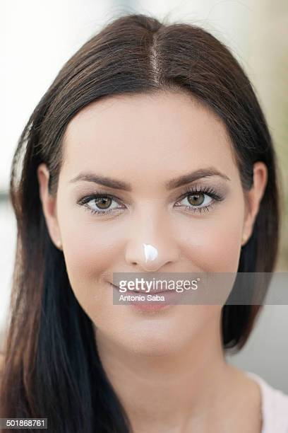 portrait of young woman with dab of cream on her nose - long nose stock photos and pictures