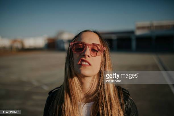portrait of young woman with defiant attitude wearing sunglasses outdoors - arrogance stock pictures, royalty-free photos & images